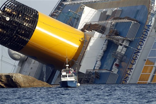 A police boat navigates near the grounded cruise ship Costa Concordia today. Rescuers on Sunday resumed searching the capsized ship for more bodies.