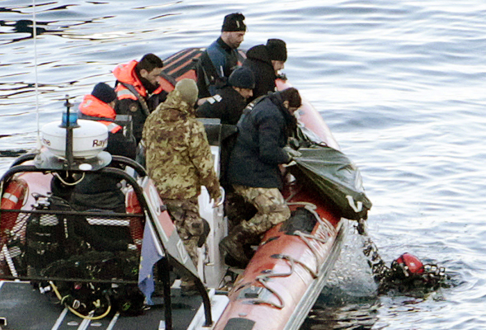 Italian naval divers recover a body from the cruise ship Costa Concordia today. Rescuers exploded four holes in the hull of the ship earlier today to gain easier access to areas that had not yet been searched.
