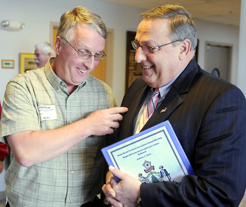 Gov. Paul LePage, right, confers Monday with Phil Bibeau of the Wood Products Manufacturers Association of Westminster, Mass., before addressing a gathering of the Maine Wood Products Association in Hallowell.