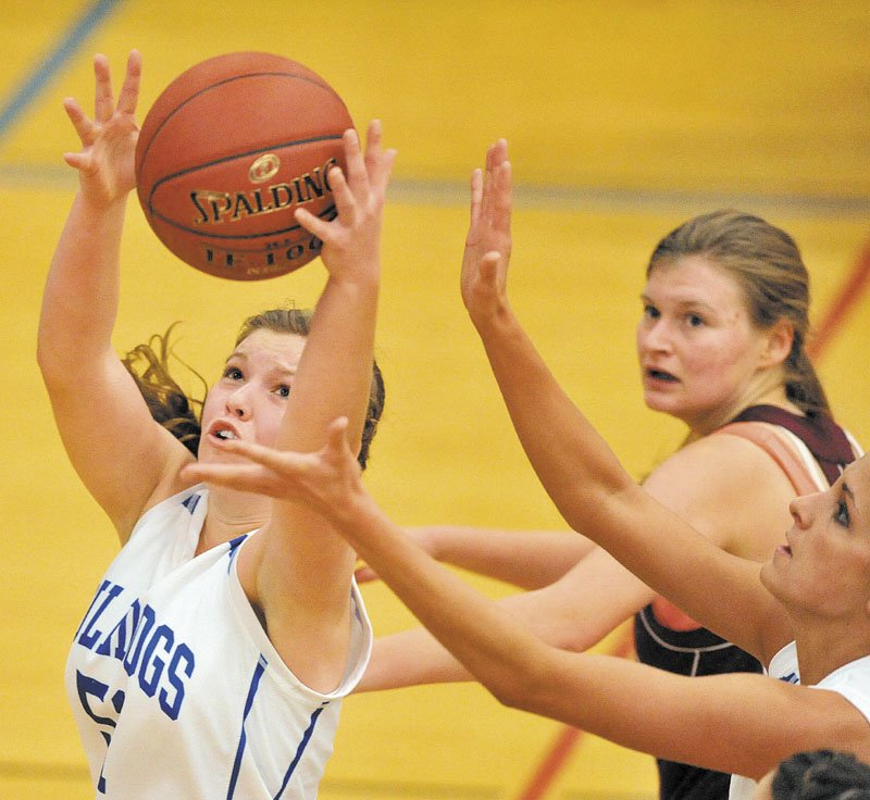 Madison's Kirsten Wood, left, grabs the rebound as Monmouth Academy's Amanda Anair, right, reaches for the ball in the second quarter Thursday night in Madison. The Bulldogs won 49-30.