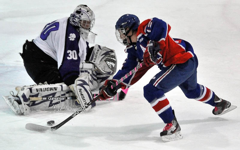 BIG NIGHT: Messalonskee's Chase Cunningham scores a goal on Waterville Senior High School's Cody Thibodeau in the first period Tuesday at Alfond Rink at Colby College in Waterville.
