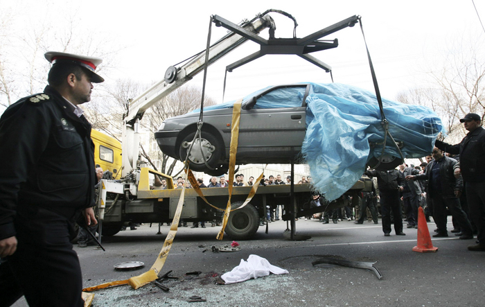 In this photo provided by the semi-official Fars News Agency, a crane removes the car of nuclear chemist Mostafa Ahmadi Roshanas today in Tehran,