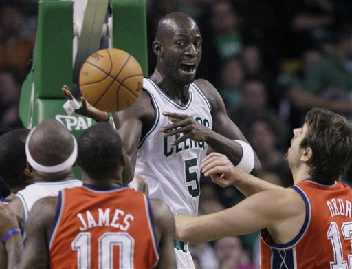 Boston Celtics forward Kevin Garnett (5) dishes the ball from under the basket as New Jersey Nets forward Damion James (10) and center Mehmet Okur (13), of Turkey, defend in the first half Wednesday in Boston.