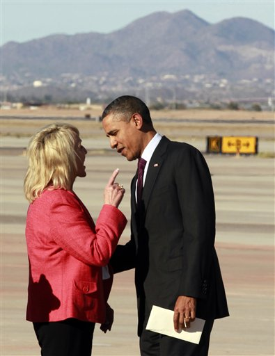 """Arizona Gov. Jan Brewer points at President Barack Obama after he arrives at Phoenix-Mesa Gateway Airport on Wednesday. The two leaders engaged in an intense conversation at the base of Air Force One's steps and both could be seen smiling, but speaking at the same time. Asked moments later what the conversation was about, Brewer, a Republican, said: """"He was a little disturbed about my book."""""""