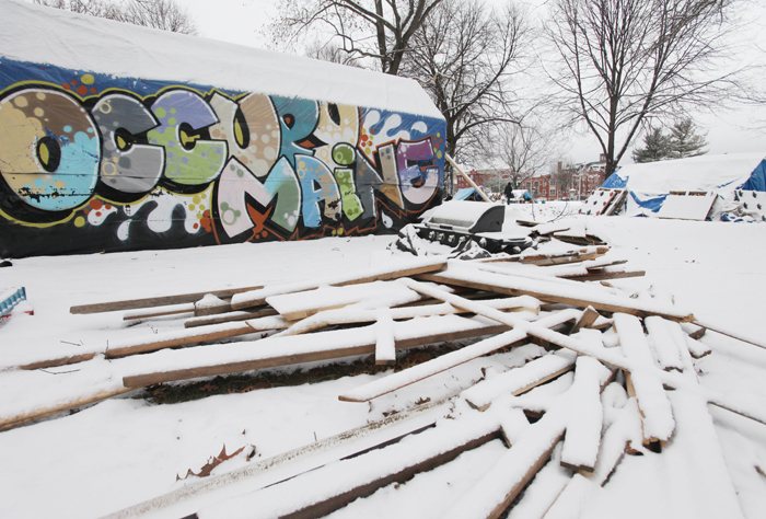 Snow covers a pile of wood at the Occupy Maine encampment in Lincoln Park in Portland. The city asked members to clean up the debris and remove unoccupied tents and structures.