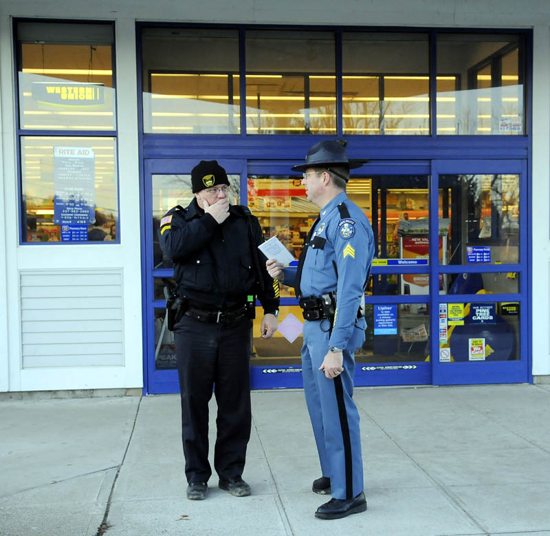 ROBBED: Gardiner Police Department Sgt. Stacey Blair, left, and Maine State Police Sgt. Micheal Field confer Monday outside the RiteAid pharmacy in Gardiner moments after it was robbed.