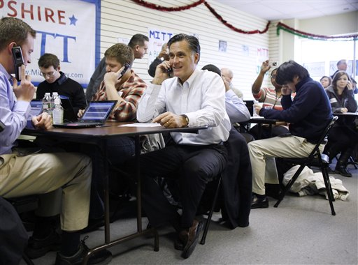 Republican presidential candidate Mitt Romney sits with volunteers to call likely voters ahead of Tuesday's primary election during a visit to his campaign headquarters in Manchester, N.H., today