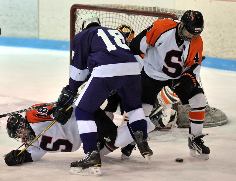 CREATING TRAFFIC: Hampden Academy's Matthew Closson, center, knocks Skowhegan Area High School's Anne Marie Provencal, left, to the ice as teammate Cam Despres tries to clear the puck from the front of Skowhegan's net during the first period Wednesday night at Sukee Arena in Winslow. Skowhegan lost 5-3.