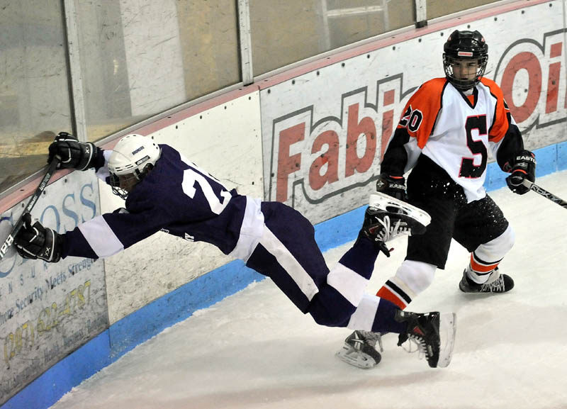 FINISH THE CHECK: Skowhegan Area High School's Chase Whittemore, 20, right, checks Hampden Academy's Kent Reichel into the boards during the first period Wednesday night at Sukee Arena in Winslow.