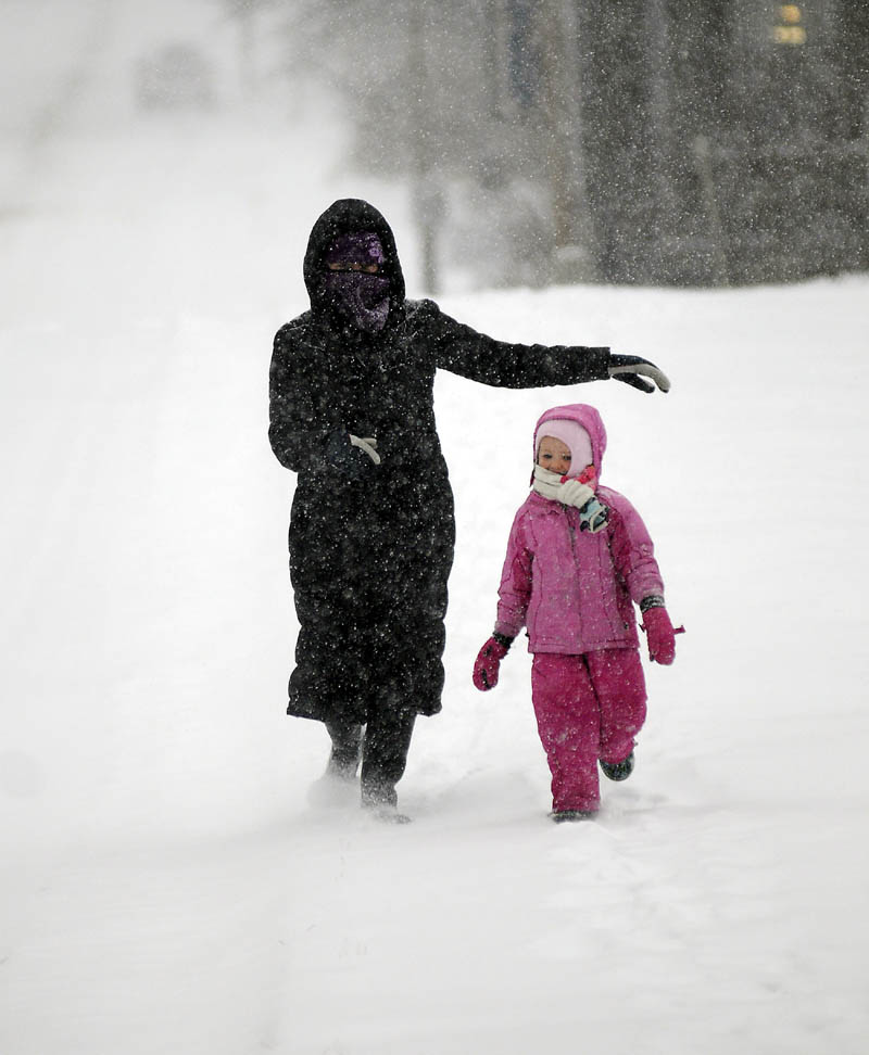 WHITE OUT: Maureen Drouin and her daughter, Lily Drouin-Scease, 4, descend Central Street in Hallowell Thursday. The couple were exploring the snow storm near their home at lunch.