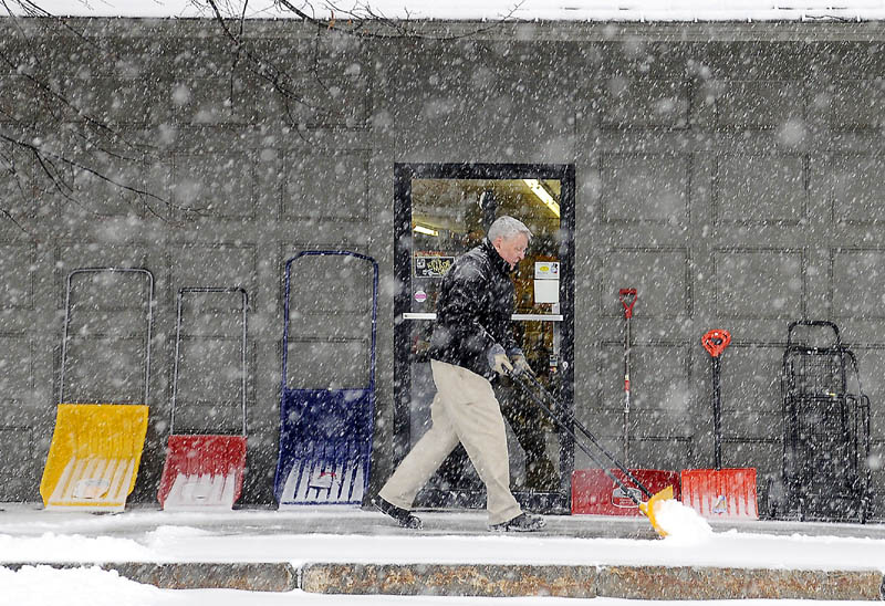 INVENTORY: Bill Harvey moves the snow Thursday that piled up in front of his Gardiner business, Harvey's Hardware. Several inches of snow of fell across Maine.