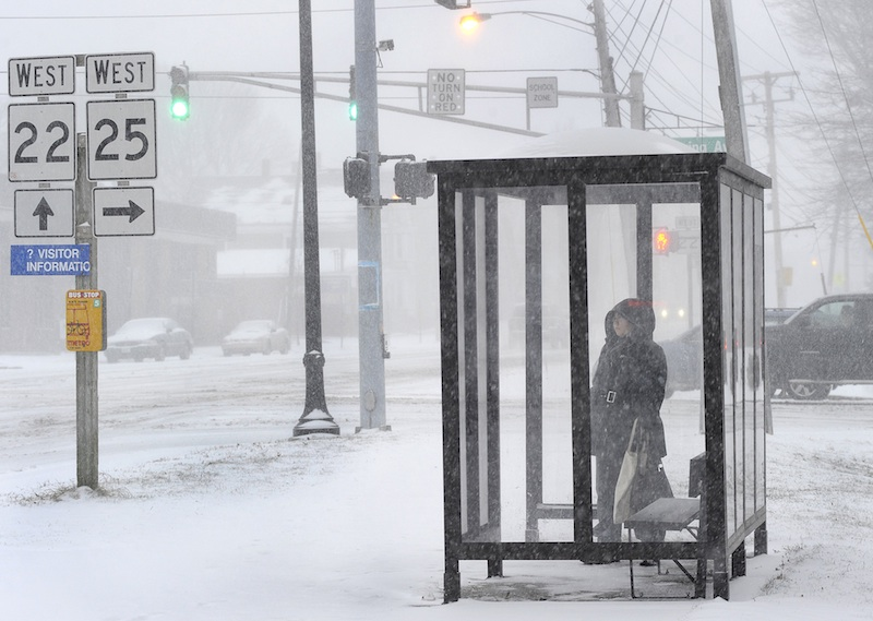 Sarah Melanson from Portland waits for a bus in a shelter along Park Ave on Thursday morning while trying to get to work. Commuters were finding the going slow as Maine receives its first snowstorm of the new year.