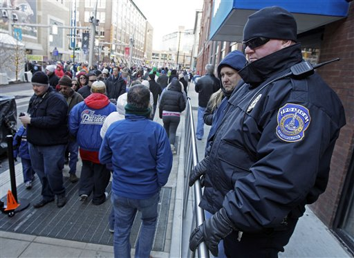 Officer David Bryant, right, of the Indianapolis Metropolitan Police, watches the crowd at the Super Bowl Village on Sunday. From pickpockets and prostitutes to dirty bombs and exploding manhole covers, authorities are bracing for whatever threat Super Bowl XLVI might bring.