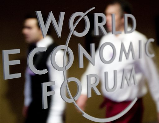 """Participants pass by a mirror with the logo of the World Economic Forum in Davos, Switzerland. The overarching theme of the meeting, which takes place today through Sunday, is """"The Great Transformation: Shaping New Models."""""""