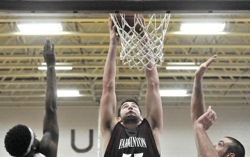 TAKE THAT: University of Maine at Farmington's Ben Johnson, center, dunks an offensive rebound over Lyndon State College defenders John Williams, left, and Jason Gray, right, in the first half Saturday at Dearborn Gymnasium at University of Maine at Farmington.