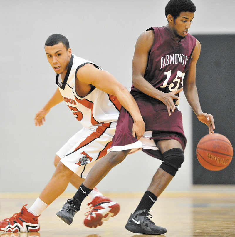 Thomas College's Ryan Newton, left, fouls University of Maine at Farmington's Yusuf Iman in the first half at Mahaney Gymnasium at Thomas College in Waterville Saturday. Thomas defeated UMF 81-73.