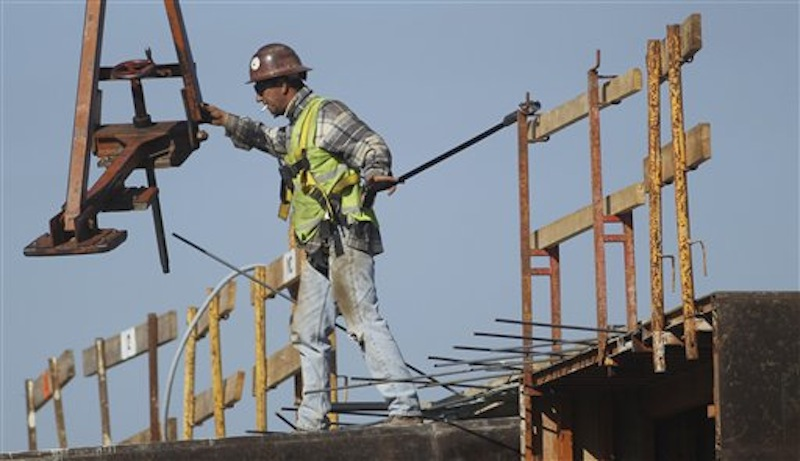 A construction worker directs a steel hoist at the foundation of a new condo complex in Sunrise, Fla. A burst of hiring in December pushed the unemployment rate to its lowest level in nearly three years. (AP Photo/J Pat Carter)