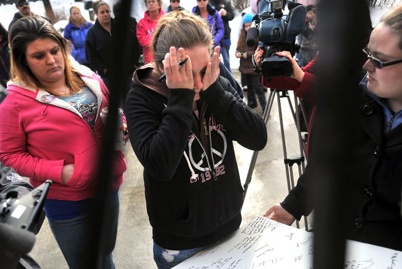 Staff photo by Michael G. Seamans Trista Reynolds, center, is over come with grief after writing a message for her missing toddler, Ayla Reynolds, during a vigil in Castonguay Square in Waterville Saturday.