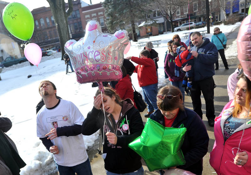 Staff photo by Michael G. Seamans Justin DePietro, far left, Trista Reynolds, center left, parents of missing toddler Ayla Reynolds, release balloons during a vigil in Castonguay Square in Waterville. Becca Hanson, right center, mother of Trista Reynolds, and Amanda Benner, far right, friend of Trista Reynolds, also are seen.