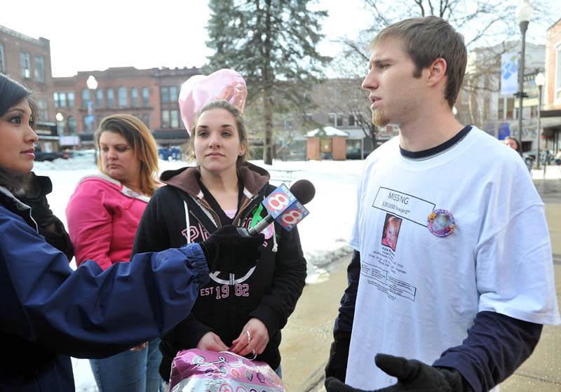 Trista Reynolds, center, and Justin DePietro, right, parents of missing toddler Ayla Reynolds, talk with media during a vigil in Castonguay Square in Waterville Saturday.