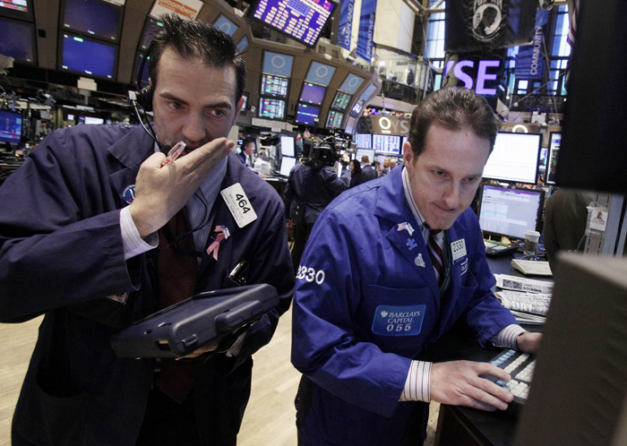 Trader Gregory Rowe, left, and specialist Glenn Carell work recently on the floor of the New York Stock Exchange.