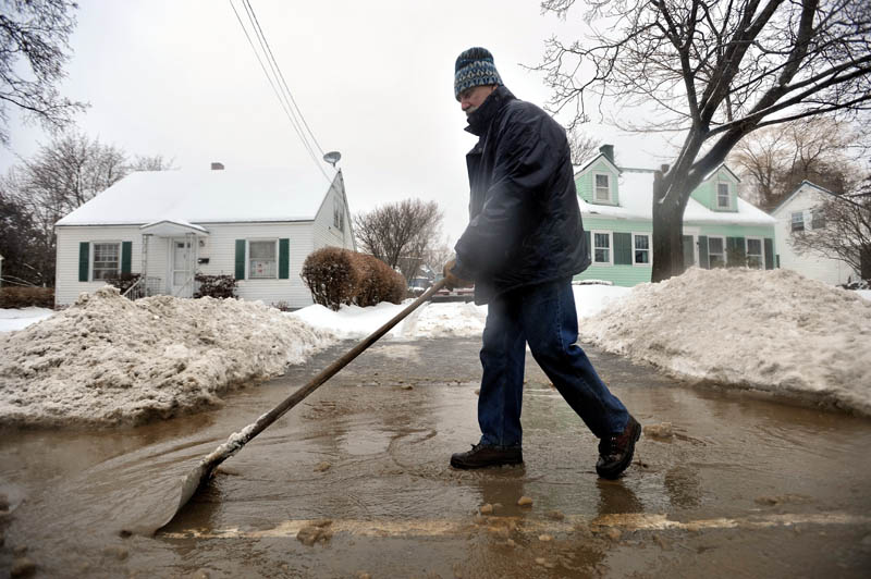 CLEARING THE WAY: Brian Bonsall clears a collecting reservior of ice water at the mouth of his driveway on North Street in Waterville on Friday.