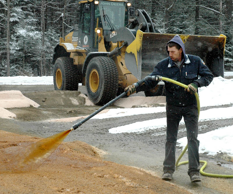 Bob Corrigan of the Skowhegan Highway Department sprays Ice B'Gone, a road de-icer made from beet molasses mixed with road salt at the town sand-and-salt yard recently.
