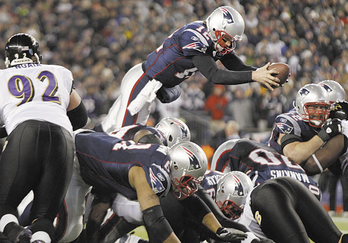 UP AND OVER: New England Patriots quarterback Tom Brady (12) dives over the middle to score on a 1-yard run against the Baltimore Ravens during the AFC Championship game Sunday in Foxborough, Mass.