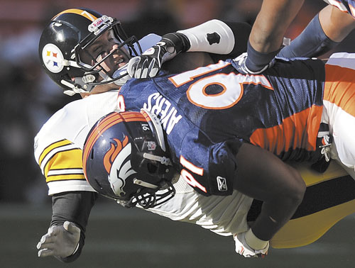 DOWN YOU GO: Denver Broncos defensive end Robert Ayers (91) hits Pittsburgh Steelers quarterback Ben Roethlisberger (7) after a pass in the first quarter of a wild card game Sunday in Denver.