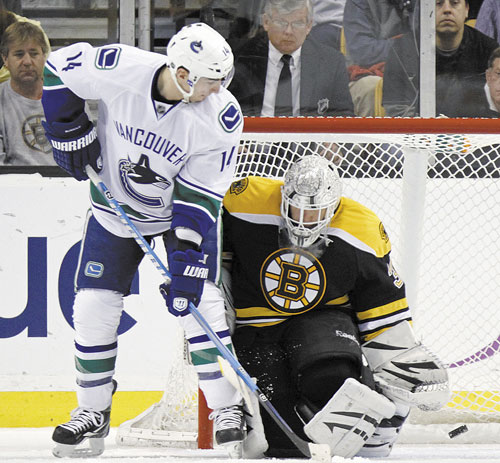 TOO LATE: Vancouver's Alex Burrows (14) watches as the puck goes into the net past Boston goalie Tim Thomas in the second period Saturday in Boston.