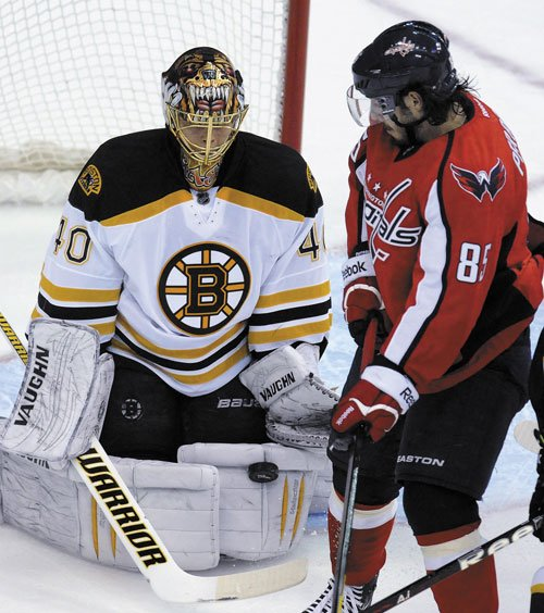 STOPPED: Boston Bruins goalie Tuukka Rask (40) stops a shot as Washington Capitals' Matthieu Perreault watches during the first period Tuesday in Washington.