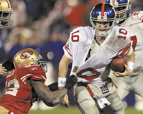 DIRTY DAY: New York Giants quarterback Eli Manning is sacked by San Francisco 49ers' Patrick Willis during the second half of the NFC Championship game Sunday in San Francisco. Manning was sacked six times in the game.