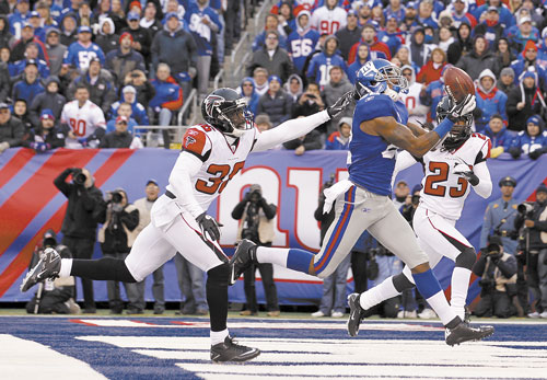 HAULING IT IN: New York Giants wide receiver Mario Manningham, center, pulls in a 27-yard touchdown pass against Atlanta Falcons strong safety James Sanders (36) and Dunta Robinson during the second half Sunday in a wild card game in East Rutherford, N.J.