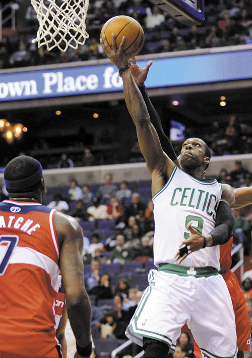 TO THE HOLE: Boston Celtics guard Rajon Rondo, right, goes to the basket against Washington Wizards forward Andray Blatche during the first half Sunday in Washington.