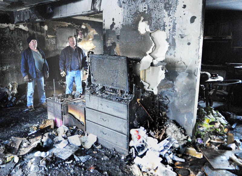 "Rodney Vigue, left, and Mike Burton survey the damage from an overnight fire in Vigue's Augusta home on Friday morning. ""It's a mess,"" Vigue said. ""The whole thing is totaled."" Vigue, 51, shares the home with his grown children and a 5-year-old grandchild. See story on B1."