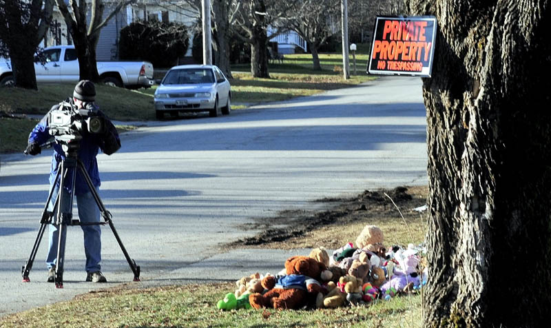 PRIVATE VS. PUBLIC INTEREST: On Monday a television news photographer films a pile of stuffed animals below a recent posting of a no trespassing sign at the home at 29 Violette Ave. in Waterville, where Ayla Reynolds was reported missing on Dec. 17.