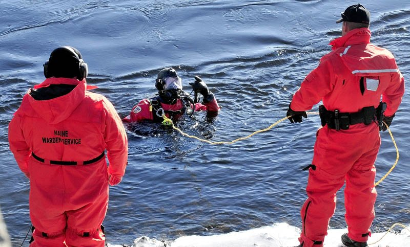 A Maine Warden Service diver comes up from the Kennebec River to speak with other wardens on the banks below the Hathaway Center in Waterville while searching for Ayla Reynolds today.