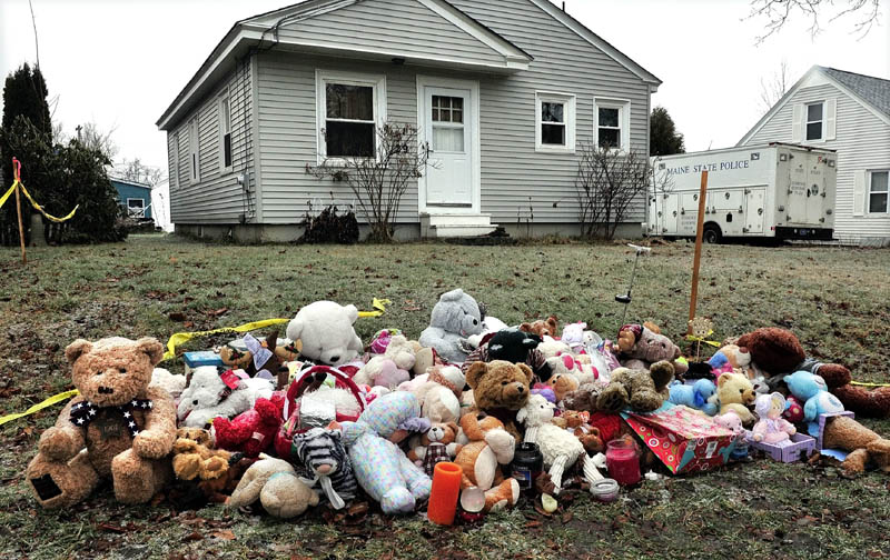 WAITING: A large pile of teddy bears and stuffed toys lies outside in the rain Saturday at 29 Violette Ave. in Waterville, near a state police crime laboratory truck parked in the driveway. The search for 20-month-old Ayla Reynolds became a criminal investigation last week.