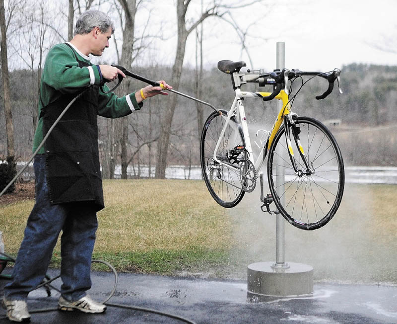 BIKE BATH: With grass and the open waters of the Kennebec River in the background, John Waller washes a bike he was servicing Thursday afternoon at Mathieu's Cycle and Fitness in Farmingdale.