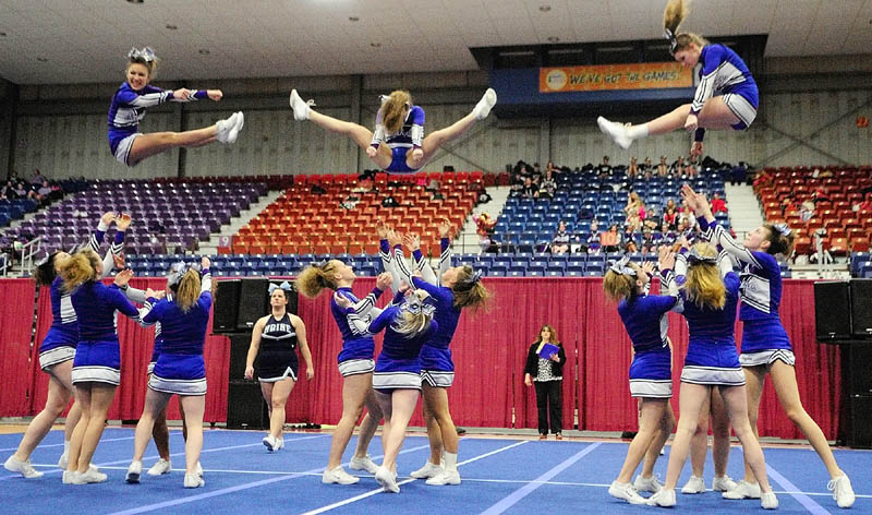 FLYING TRIO: Three Erskine Academy flyers leap into the arms of teammates during their routing at the Eastern Maine Class A cheerleading competition Saturday night at the Augusta Civic Center.
