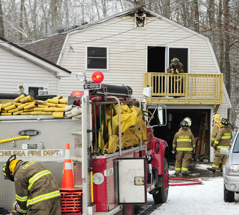 Chelsea firefighters pack up after extinguishing a fire in the second floor over a garage on Norway Road in Chelsea on Saturday morning.