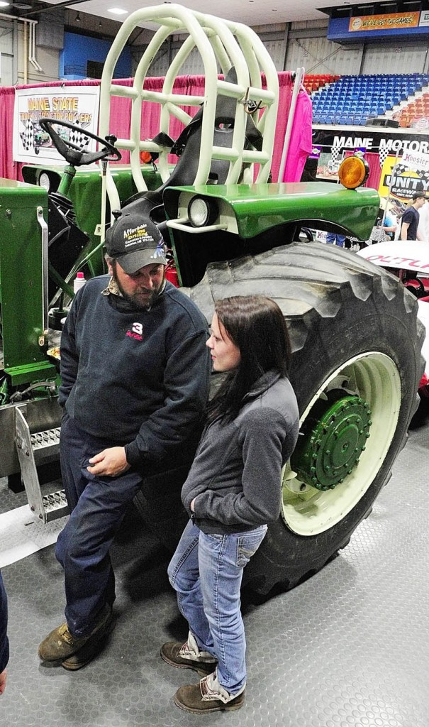 BIG TRACTOR: Phil Bisson, left, stands next to his 9,300-pound class pulling tractor and chats with Outlaw class driver Rachel Dubois during the opening night of the Northeast Motorsports Expo on Friday evening at the Augusta Civic Center.