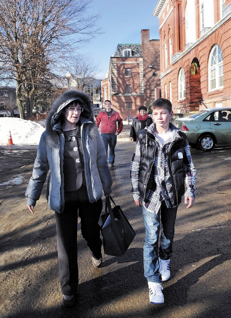 TOUR: Arina Pavlova and Anton Yeltsov of Kotlas, Russia, walk in Waterville after touring city hall followed by area hosts Mark Fisher and Martha Patterson. Waterville and Kotlas are sister cities.