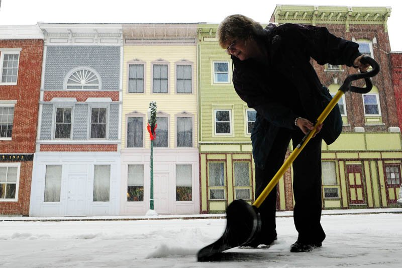 Ann Ebert shovels snow in front of Lisa's Legit Burritos during the first snow storm of the year on Thursday morning in downtown Gardiner.