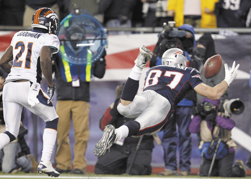 New England Patriots tight end Rob Gronkowski (87) reaches out to catch a 10-yard touchdown pass while being defended by Denver Broncos cornerback Andre' Goodman (21) during the first half Saturday in Foxborough, Mass. playoff playoffs
