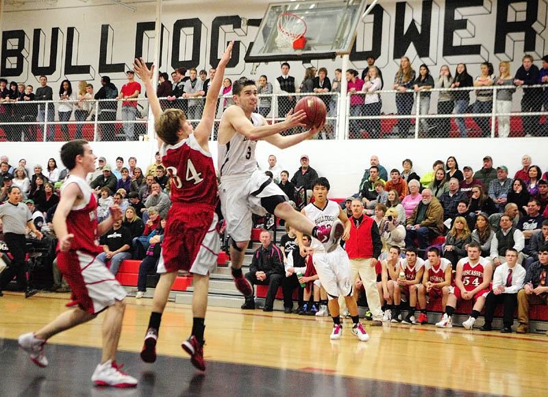 DRIVING BY: Hall-Dale's Mike Woods, right, goes up for a shot as Wiscasset's Travis Padilla (34) tries to stop him during a game Friday night in Penny Memorial Gym at Hall-Dale High School in Farmingdale.