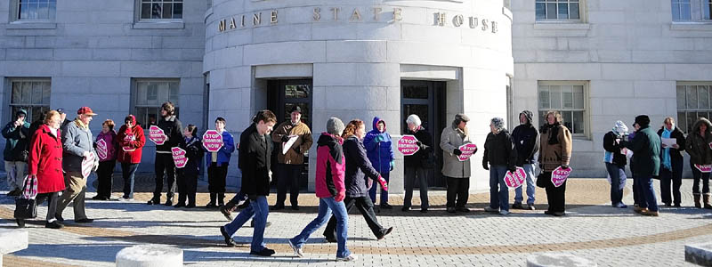 """Protetsters ring the State House on Saturday afternoon in Augusta as part of the annual """"Hands Around the Capitol Rally and March."""""""