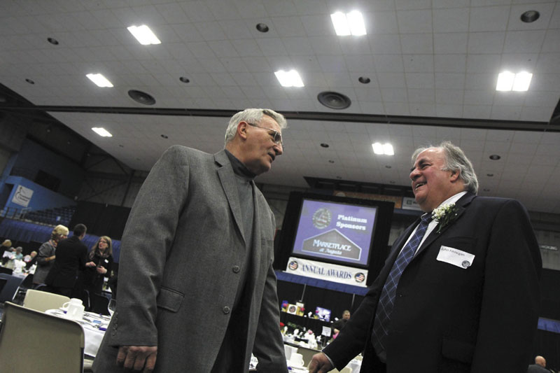 John Finnegan, president of Macomber, Farr & Whitten, right, chats with lifelong friend Richard Boucher of Augusta prior to receiving the Business Person of the Year award at the Kennebec Valley Chamber of Commerce's annual awards banquet at the Augusta Civic Center on Friday night.