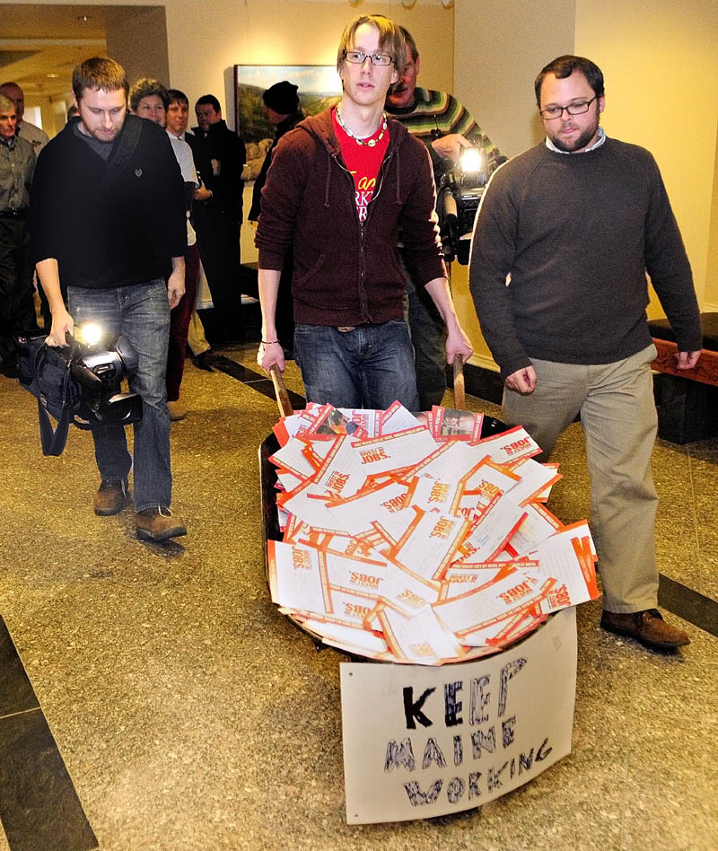 Staff photo by Joe Phelan Matt Caston, center, and Charlie Urquhart, of Working America, are followed by videographers as they deliver a wheelbarrow of post cards to Gov. Paul LePage's office in the Augusta's State House on Wednesday morning.