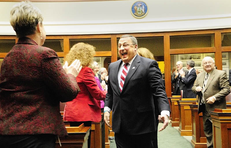 Gov. Paul LePage, right, greets Rep. Joyce Maker, R- Calais, as he walks down the aisle to give his first State of The State address on Tuesday evening at the State House in Augusta.